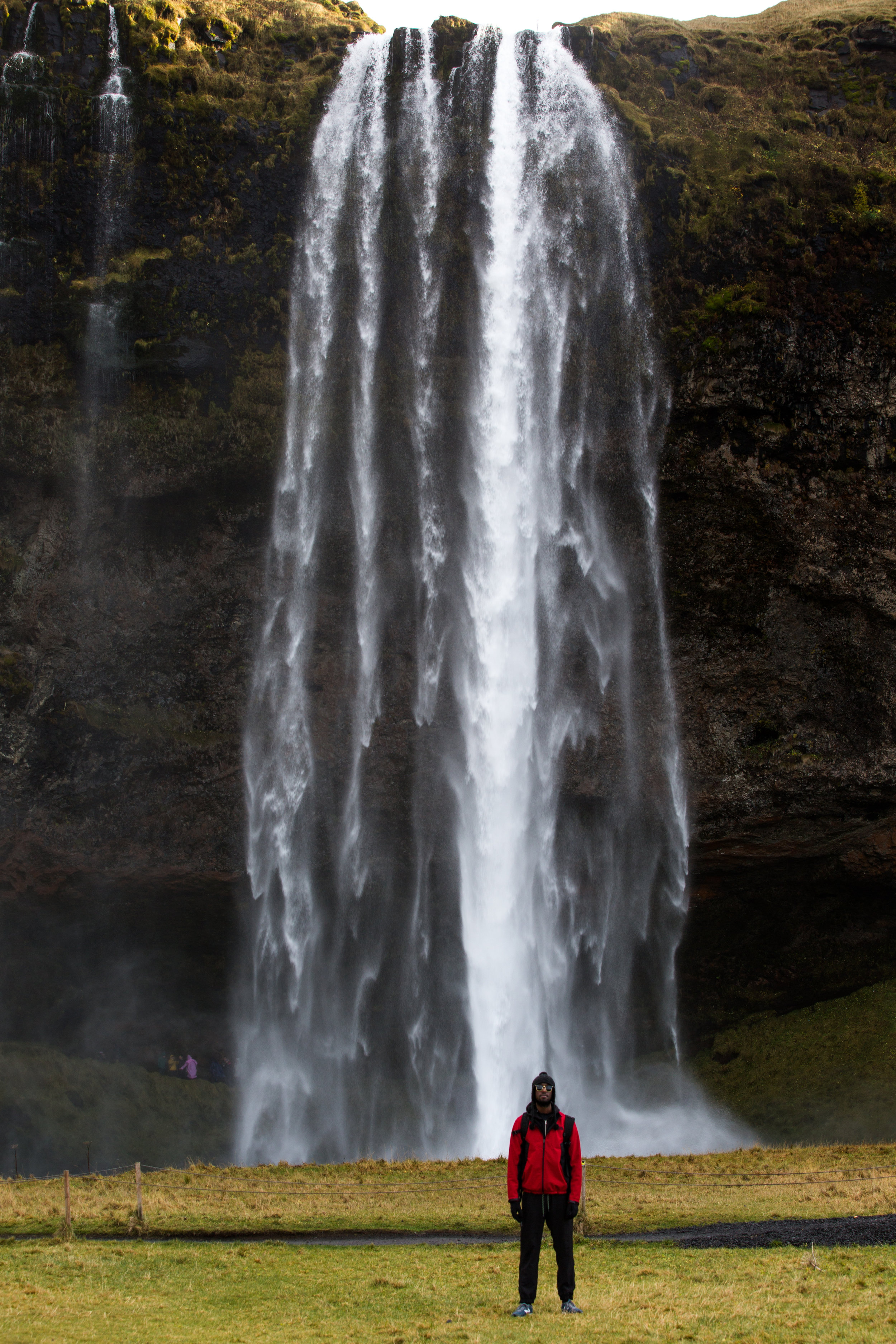 Giants standing among giants. Seljalandsfoss is a 60 meter waterfall that is part of the Sejalands River. Born from the volcanic glacier Eyjafjalla, it's normally know as the waterfall that you can walk behind through a carved mountain wall.