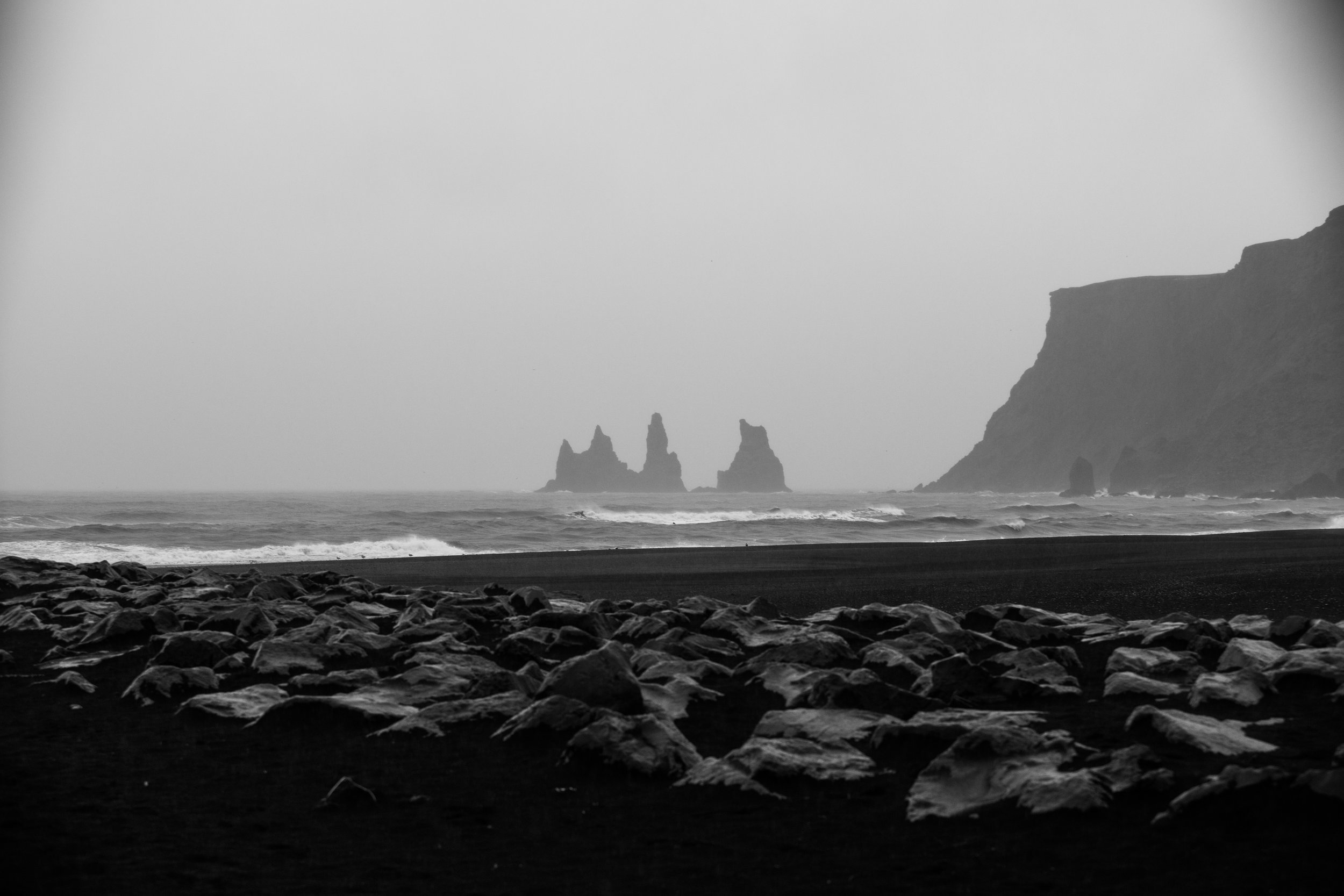 The small coastal town of Vik met us with heavy rain, the air smelling faintly of wet ash. Wind made salt crystals settle in any crevices not tightly wound in rain gear. The towers in the distance are named Reynisdrangar; formed of ancient basalt deposits in the area. Nordic folklore says two trolls tried to drag a ship to land one murky night, but were turned to stone when sunlight hit them, trapping them here indefinitely. The entirety of the beach is a fine black sand chilly paradise from the vast swathes of volcanic ash spilled at the edges of much the Icelandic coasts.