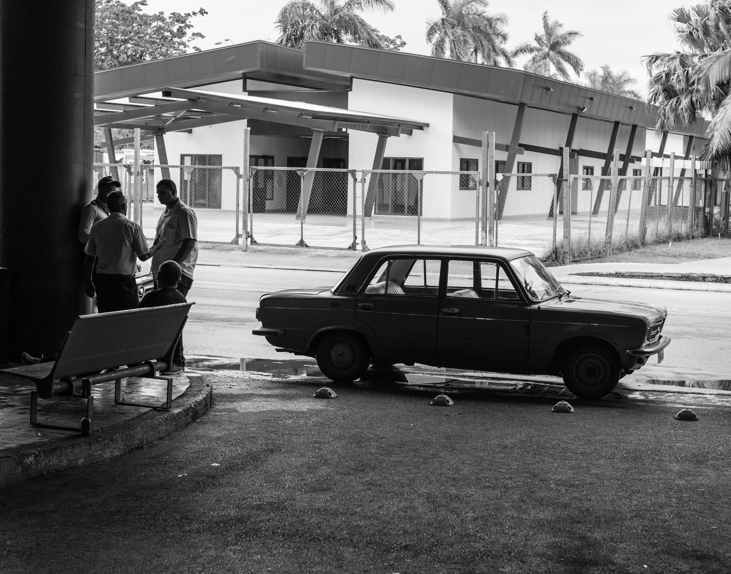Cab drivers have a smoke while waiting near terminal 3 at Havana's José Martí International Airport with a Russian made classic.