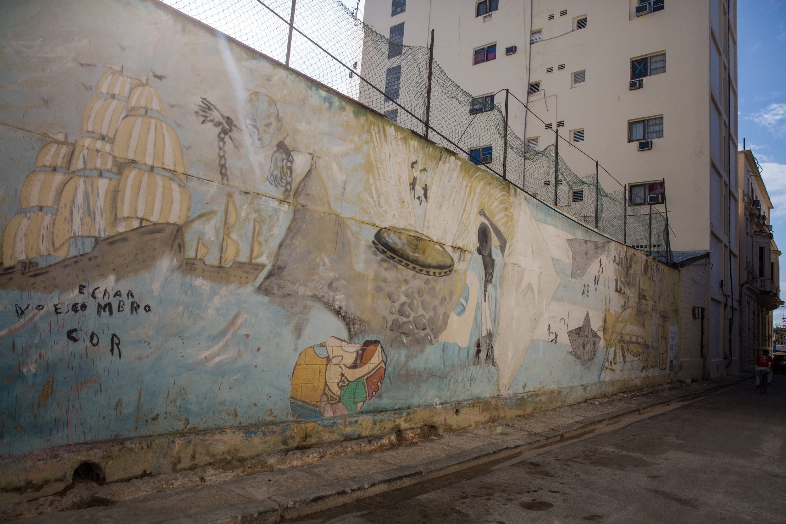 An old mural of a cartoon was covered up, over it a scene of Spanish ships, and African slaves beating drums and floating with spectral chains.