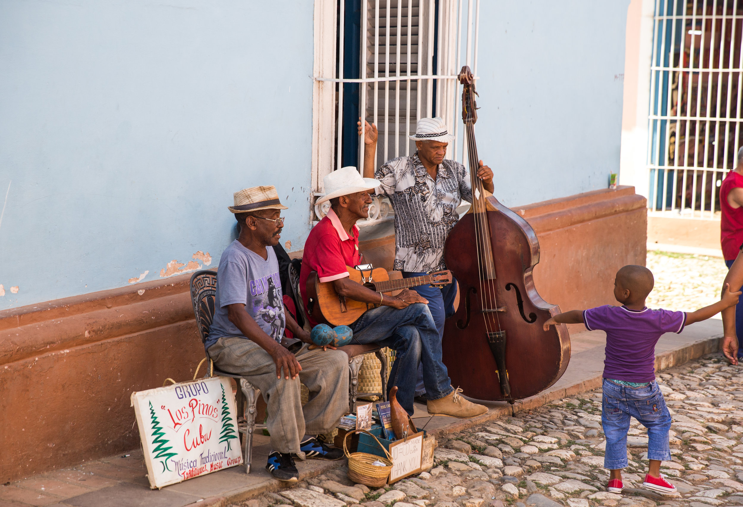 Los Pinos takes a break while a young Cuban boy admires the trio.