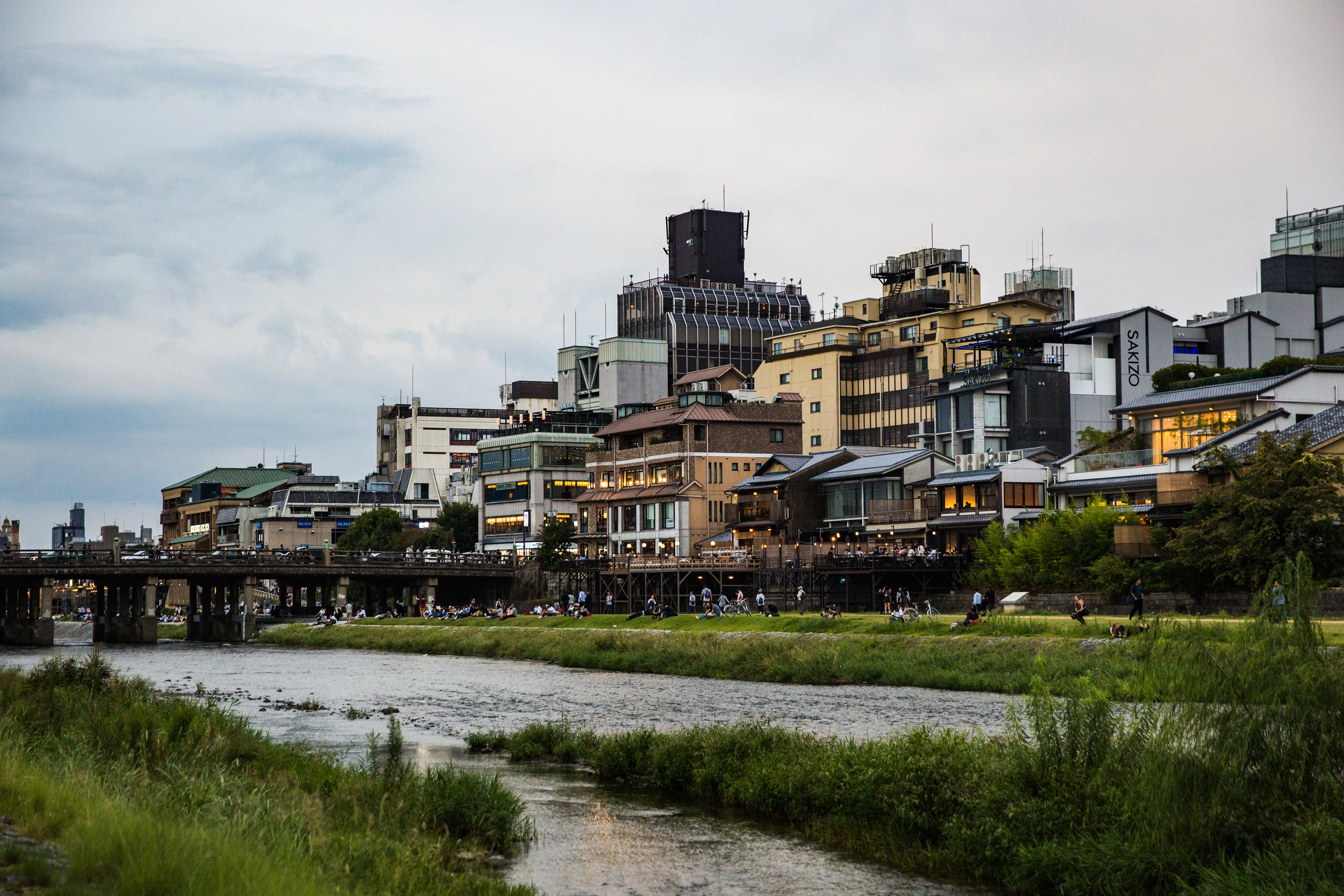 Locals and tourists alike enjoy the riverbank before making their way to Pontocho Alley for shopping, food, and sightseeing.