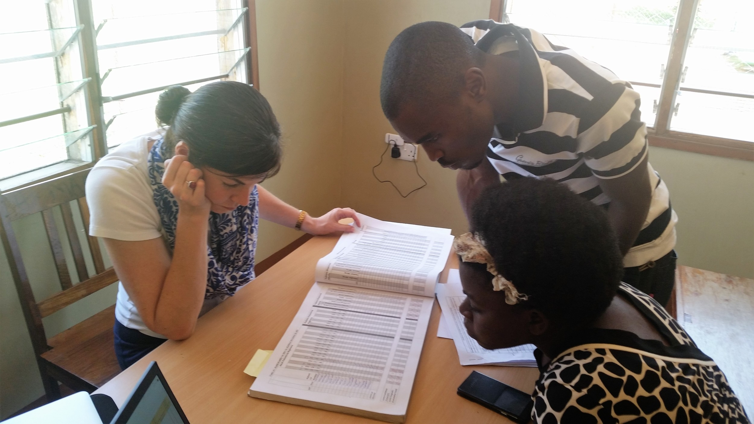 Collecting data about mother-to-child HIV transmission with Research Assistants Agatha and Kassim at Tinde Health Center in Shinyanga Region, Tanzania