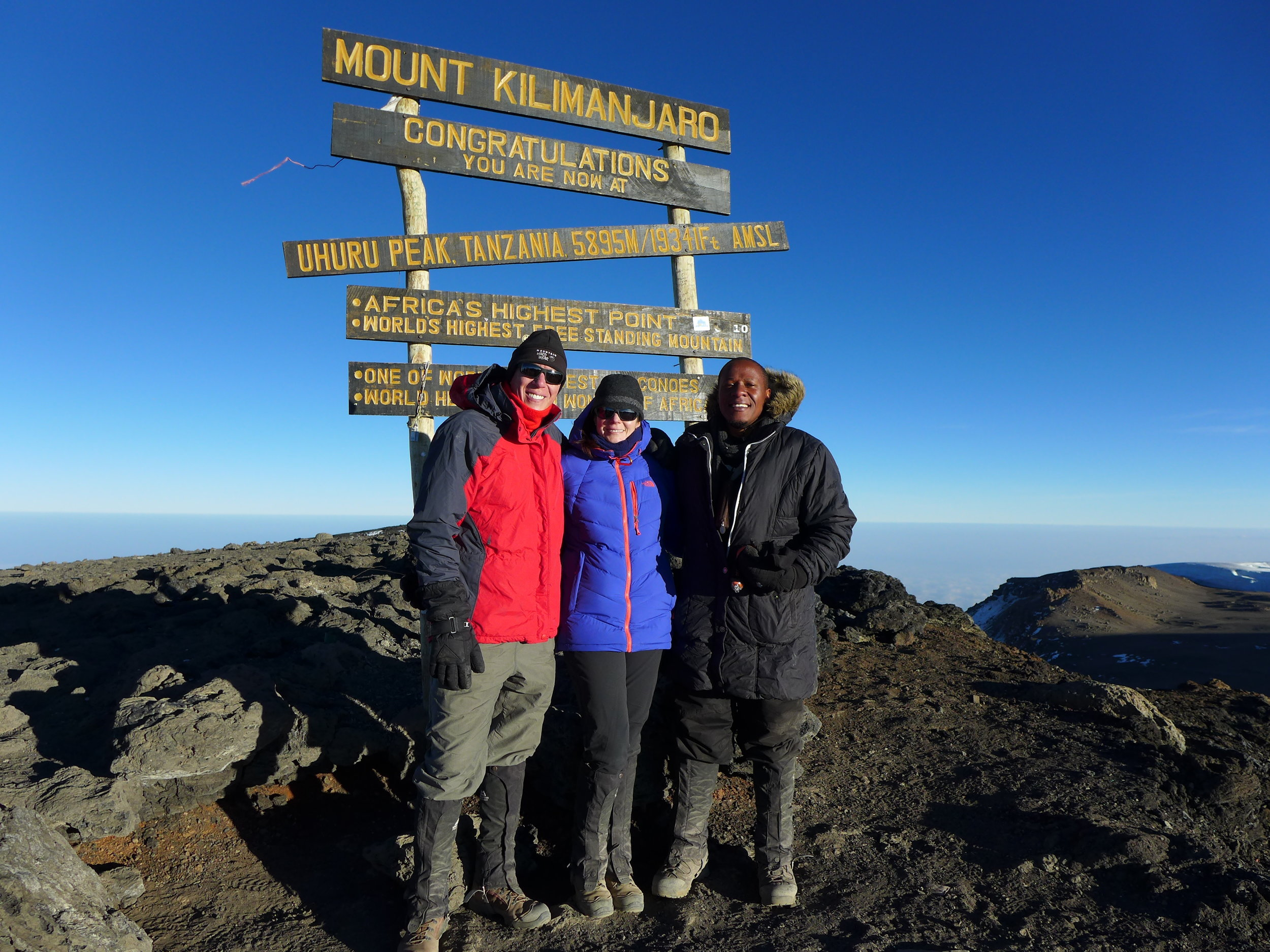 Sandi, her husband Brian Lewis, and long-time collaborator Dr. Prosper Njau at the top of Mount Kilimanjaro.
