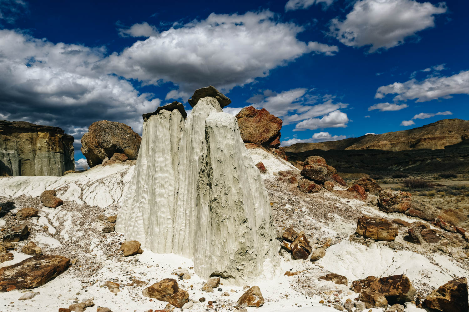 The soft entrada sandstone is pure white in color and forms hoodoos that are often topped either by dark sandstone blocks or unusual boulders of purple conglomerate, composed of small pebbles bonded together.