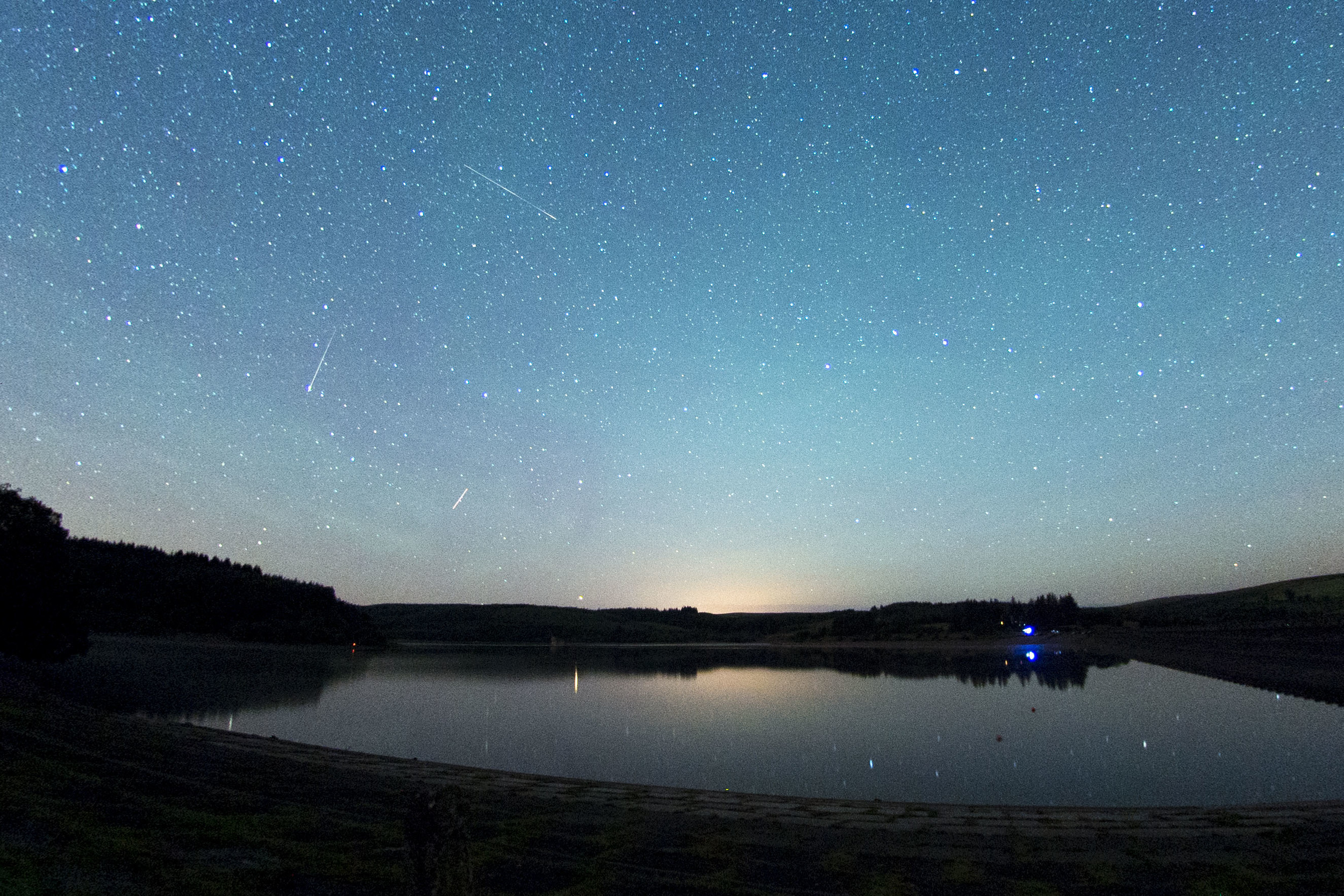 Perseid Meteor Shower 2015 at Usk reservoir, Brecon. The Perseids are pieces of Comet Swift-Tuttle - each August, the Earth passes through a cloud of the comet's debris.