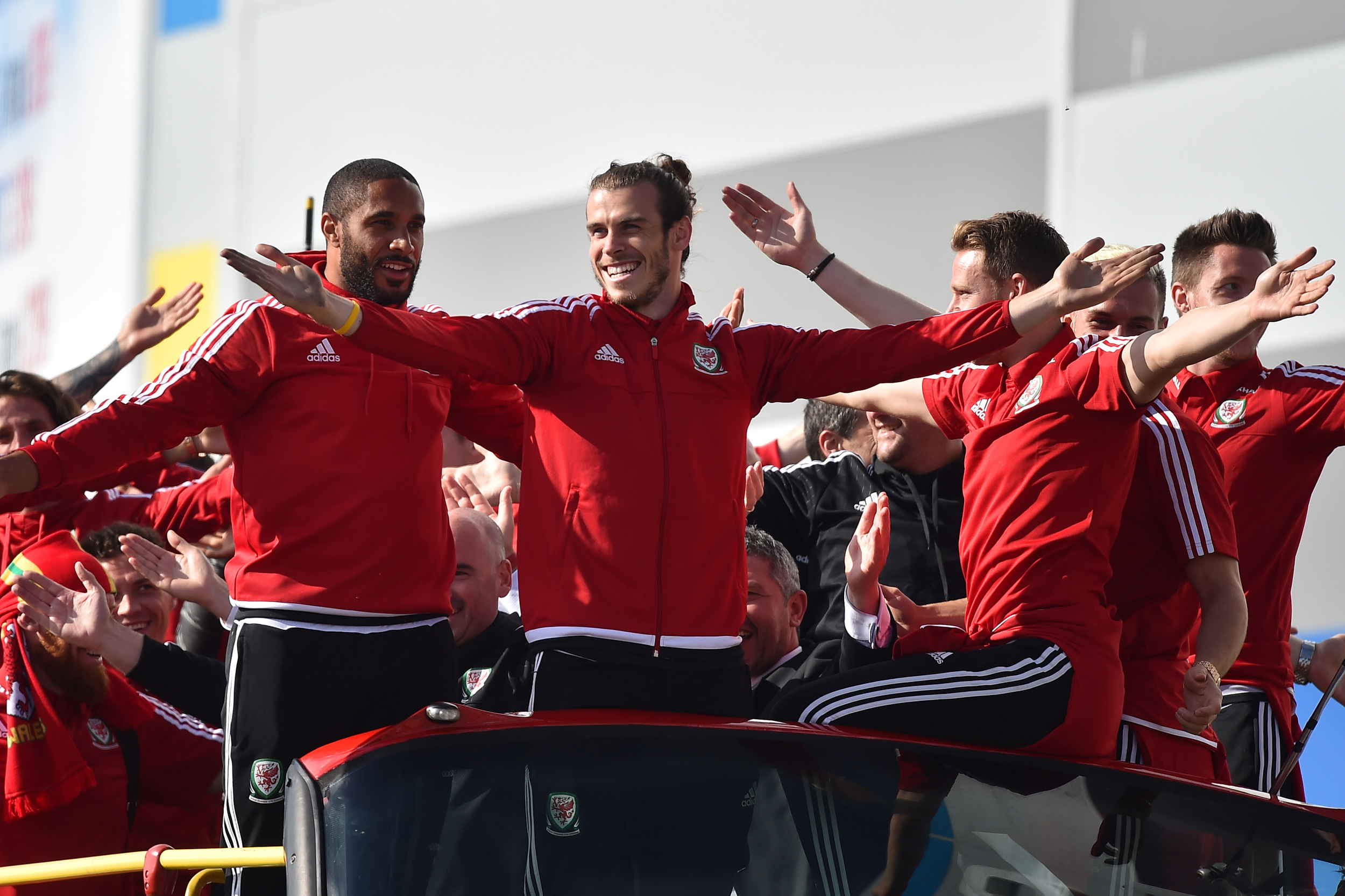 CARDIFF, WALES - JULY 08: Wales football players Ashley Williams (Left) with Gareth Bale (Centre) as the open top bus arrives at the Cardiff City Stadium on July 8, 2016 in Cardiff, Wales. The players toured the streets of Cardiff in an open top bus before arriving at the Cardiff City Stadium for an after party for which 33,000 tickets have been sold. Wales historic run in Euro 2016 saw them reach the semi-finals, before being knocked out 2-0 by Portugal at Stade de Lyon in France. (Photo by Matthew Horwood/Getty Images)