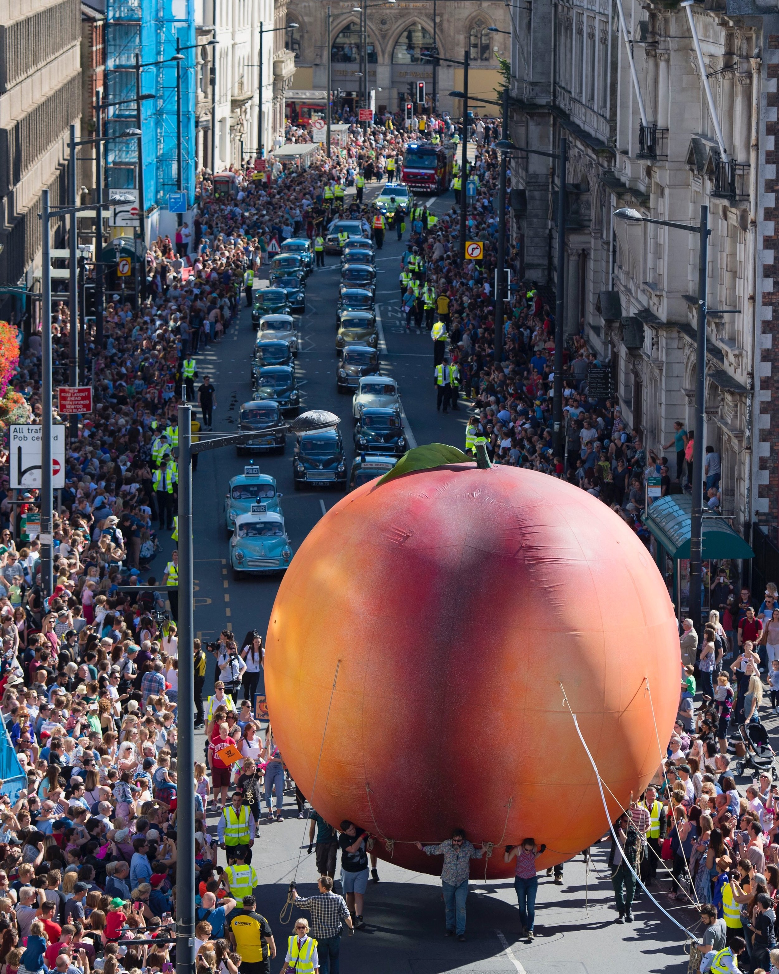 A giant peach makes its way down Westgate Street in Cardiff, South Wales during the Roald Dahl City of the Unexpected event.