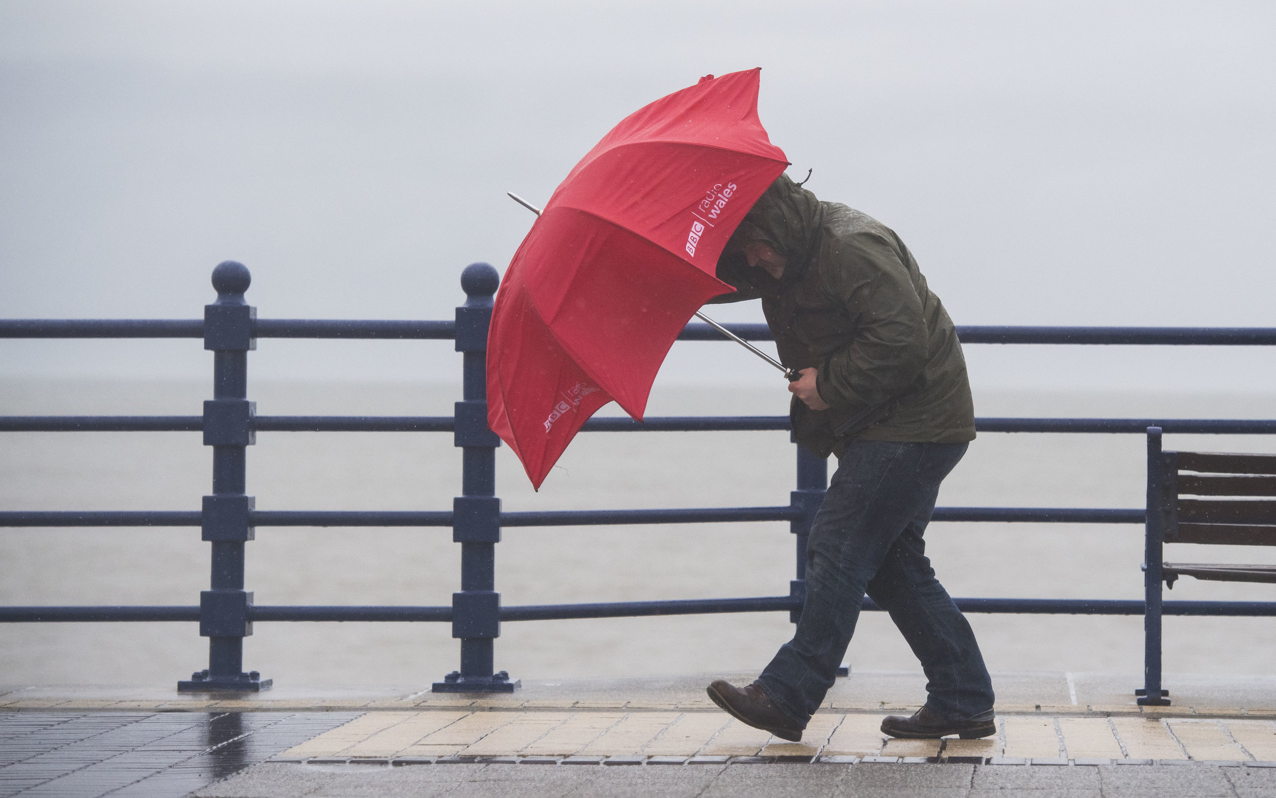 A man battles through wind and rain during Storm Angus at Porthcawl, South Wales. The met office have issued a weather warning for rain for Wales. (Photo by Matthew Horwood)