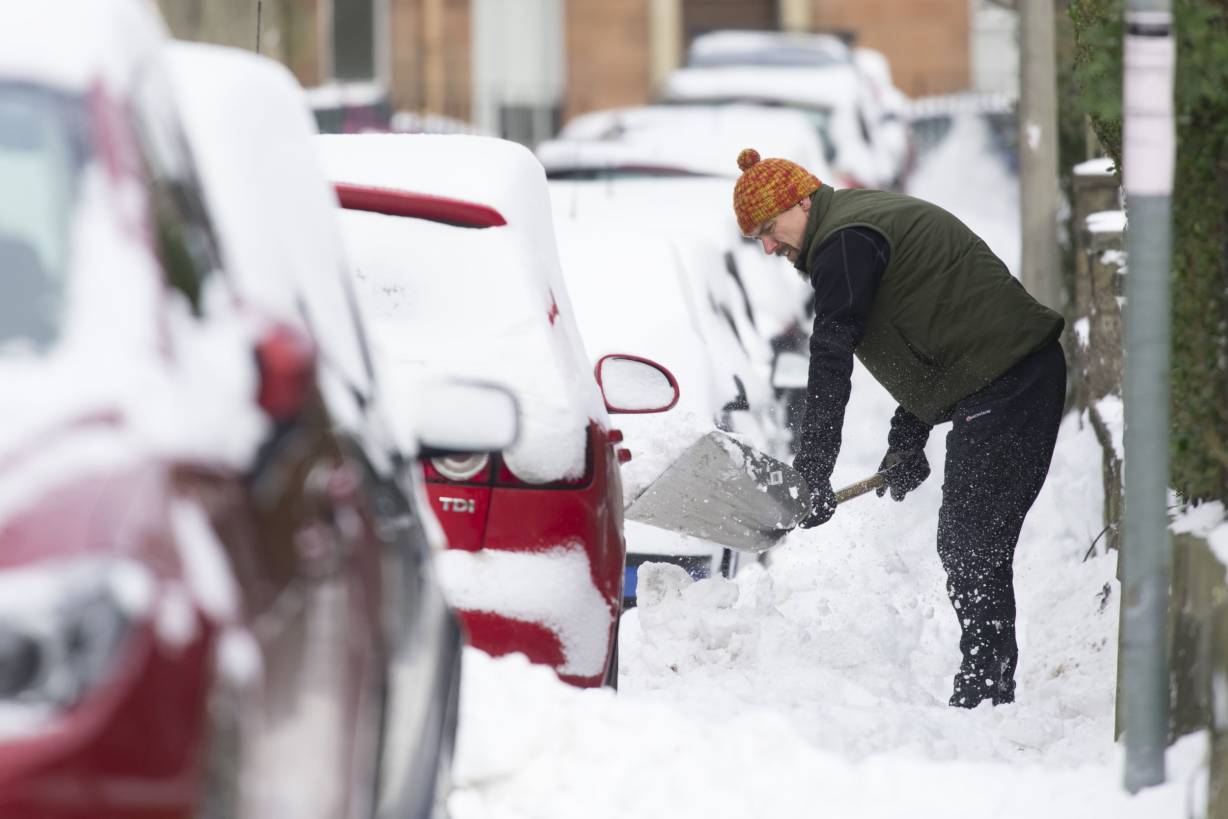 EDINBURGH, SCOTLAND - MARCH 1: A man clears snow from the pavement on March 1, 2018 in the Abbeyhill area of Edinburgh, United Kingdom. People have been warned not to make unnecessary journeys as the Met office issues a red weather be aware warning for parts of Wales and South West England following the one currently in place in Scotland. (Photo by Matthew Horwood/Getty Images)
