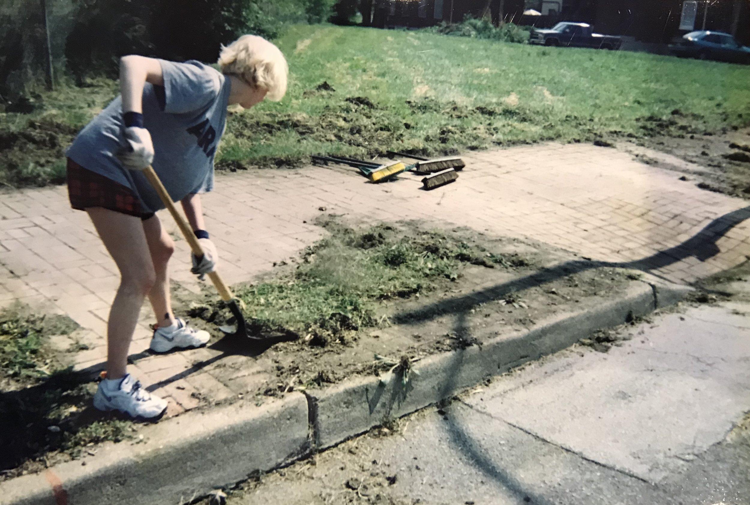 A volunteer cleans Soulard's brick sidewalks
