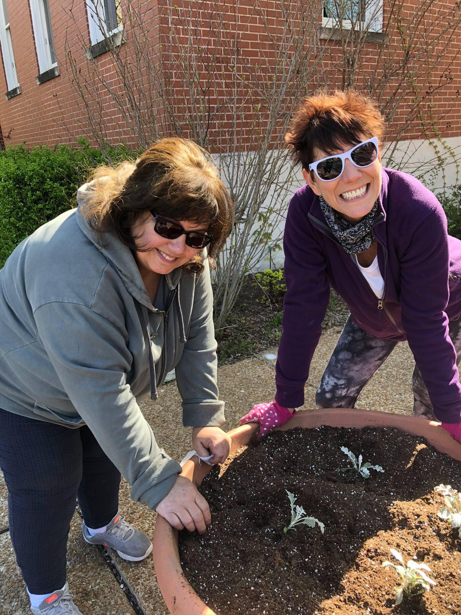 Volunteers Beth Bennett and Julie Dinkelmann plant a pot
