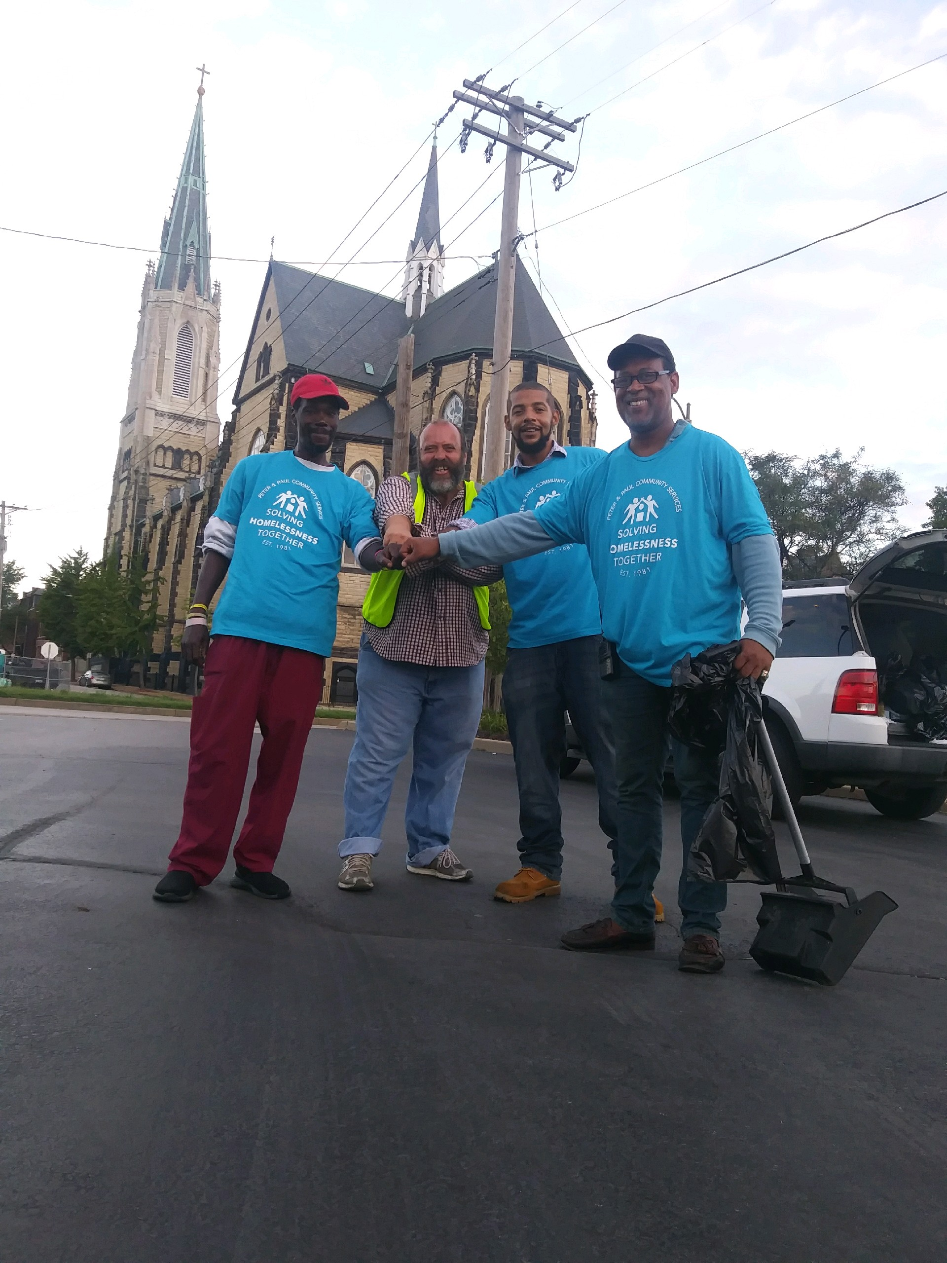 Members of the Soulard Clean Team pose in front of Sts Peter and Paul Catholic Church