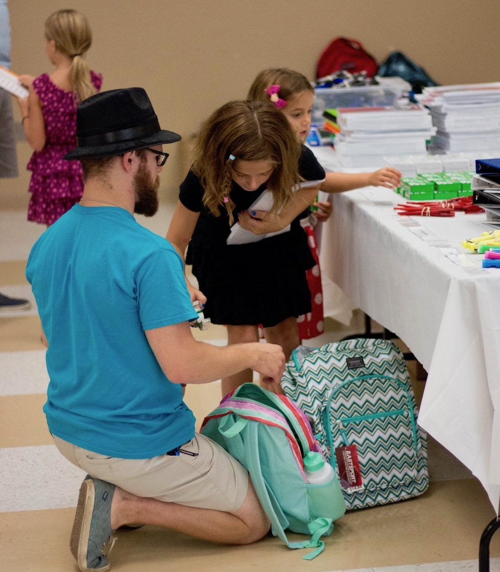 A volunteer helps a child pack a backpack at the 2017 SPLASHserves event