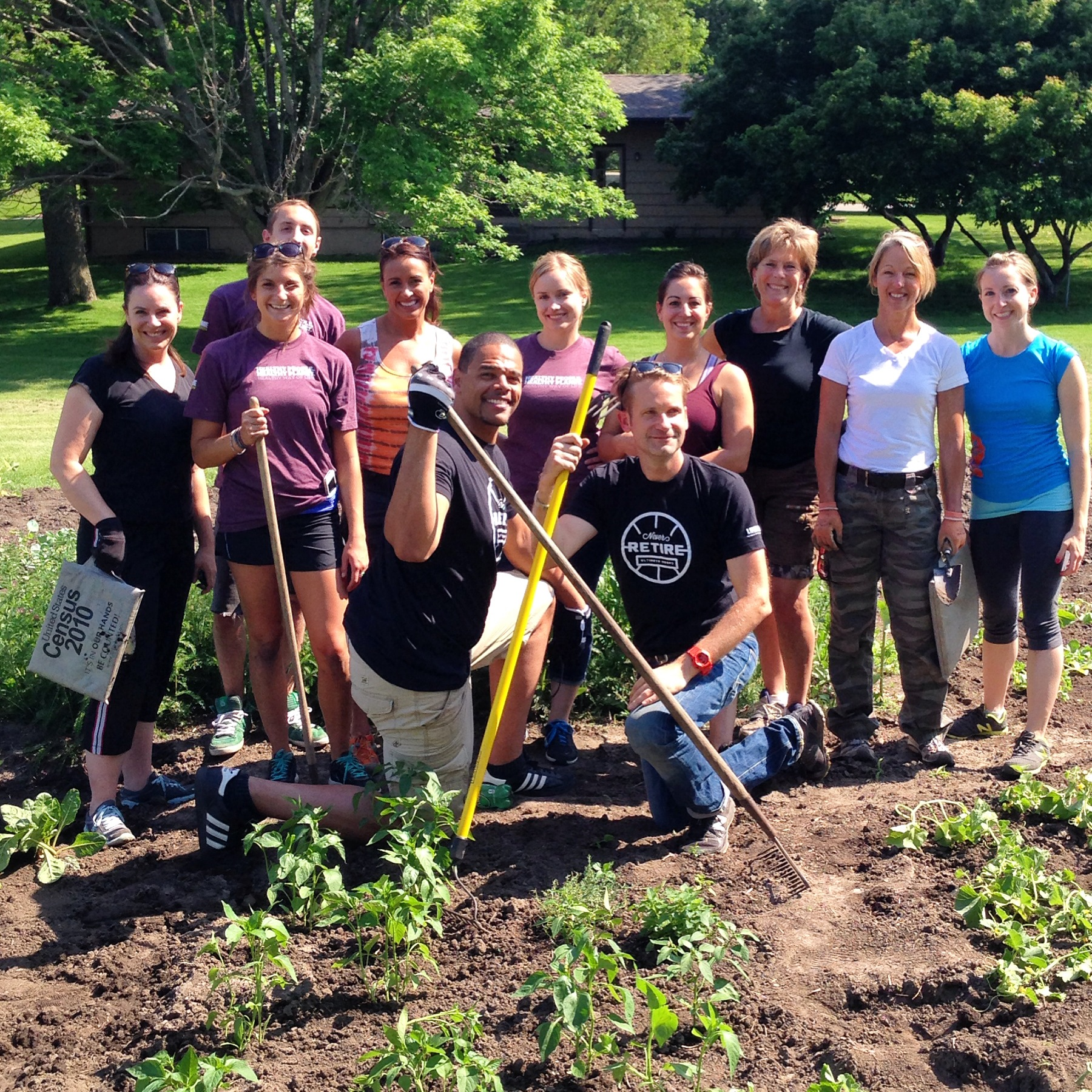 Ultimate Hoops' John Thomas (kneeling left) and Alan Arlt (kneeling right) volunteered with others from Life Time Fitness to help Grow.Eat.Share.