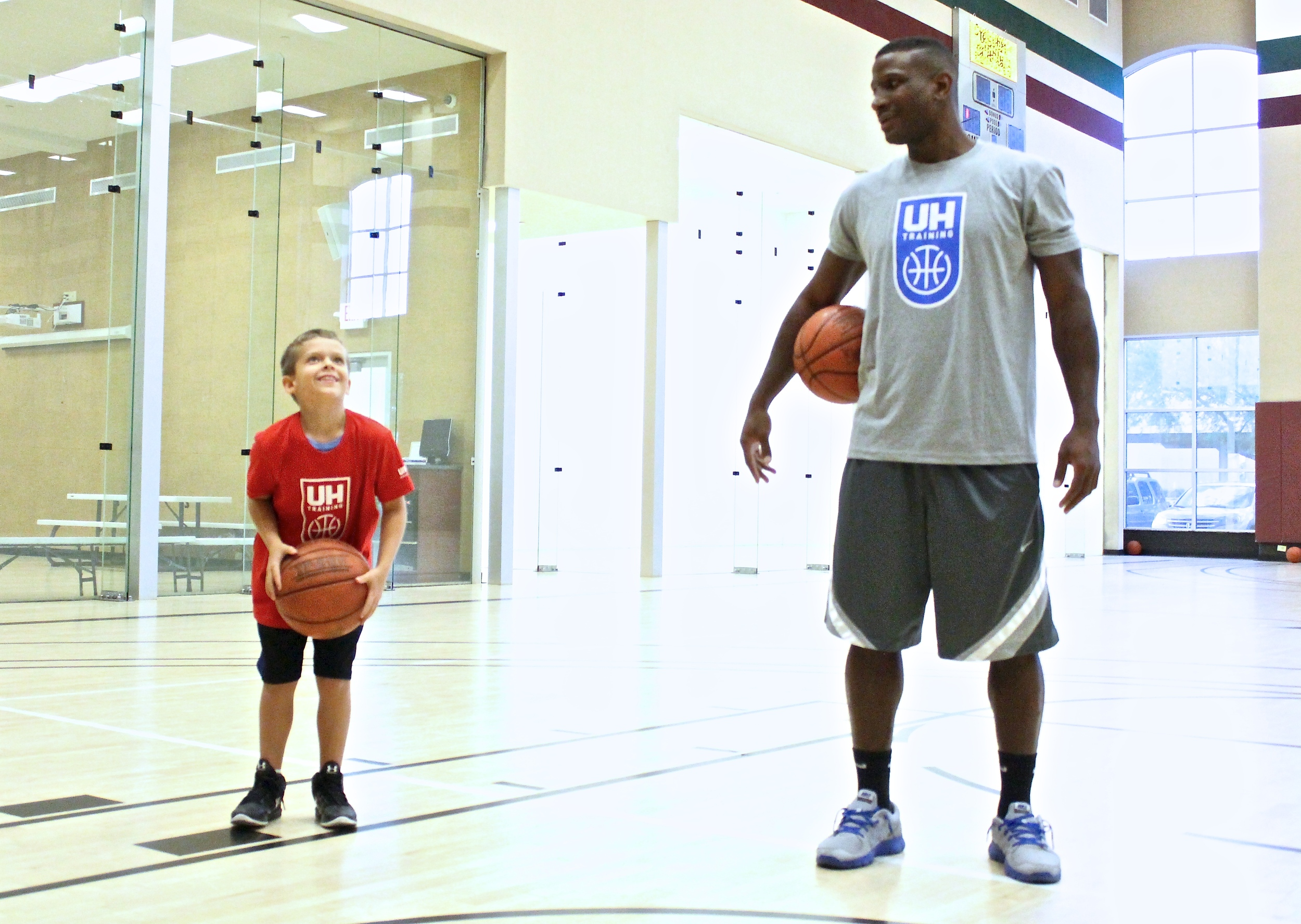 John McFall Jr. eyes up the basket under the watchful eye of his Ultimate Hoops basketball trainer, Tyrone Jones. McFall was diagnosed with Leukemia in 2015. (photo by Donald Dangmuk)