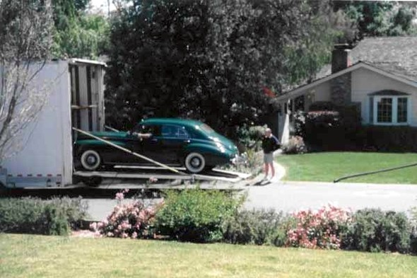 He was without an old car for a number of years, but that changed in 2005, when he acquired a 1941 Packard Clipper sedan. The history of our Packard is interesting. Its original owner was the rich widow of the owner of a coal mine in West Virginia. When she died, the car went to her niece, who drove it for a few years. There were a few short-term owners and it then ended up in a museum in West Virginia. The museum sold it to a private owner, who drove it home to Phoenix, Arizona. When he died, his wife sold it to Roy. Here is a picture of the exciting day when it arrived and was unloaded at our front door in February 2005.