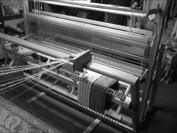 The ends of kid mohair yarn are wound, one inch at at time, onto the back beam of the loom. Yes, it is turned by hand, yards and yards of it!