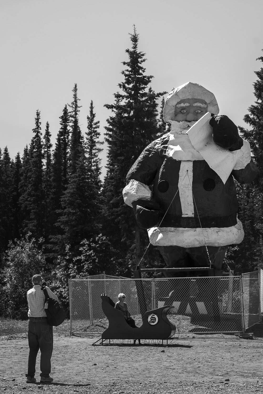 turister fotograferar jultomten mitt i sommaren i North Pole Alaska