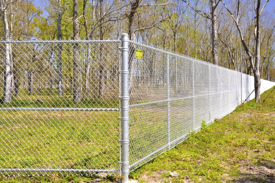 Chain Link Fence    A chain-link fence (also referred to as a wire netting, wire mesh, chain wire, cyclone or hurricane) is usually made from galvanized or galvanized wire that has been dipped in vinyl, and then woven to form a zig zag, or diamond pattern. We commonly stock 3, 4, 5, 6 & 8′ foot tall fence for installation although almost any height is possible. Common gauges are 11.5 for residential and 9 for commercial. Public works fencing is general 9 gauge and 10 foot tall for say a tennis court, or ball park. The popularity is derived from its relatively low cost of ownership and ease of installation. A further advantage is from its transparency from either side of the fence. If semi-opaque fencing is desired, this is achieved by the insertion of slats into the mesh.
