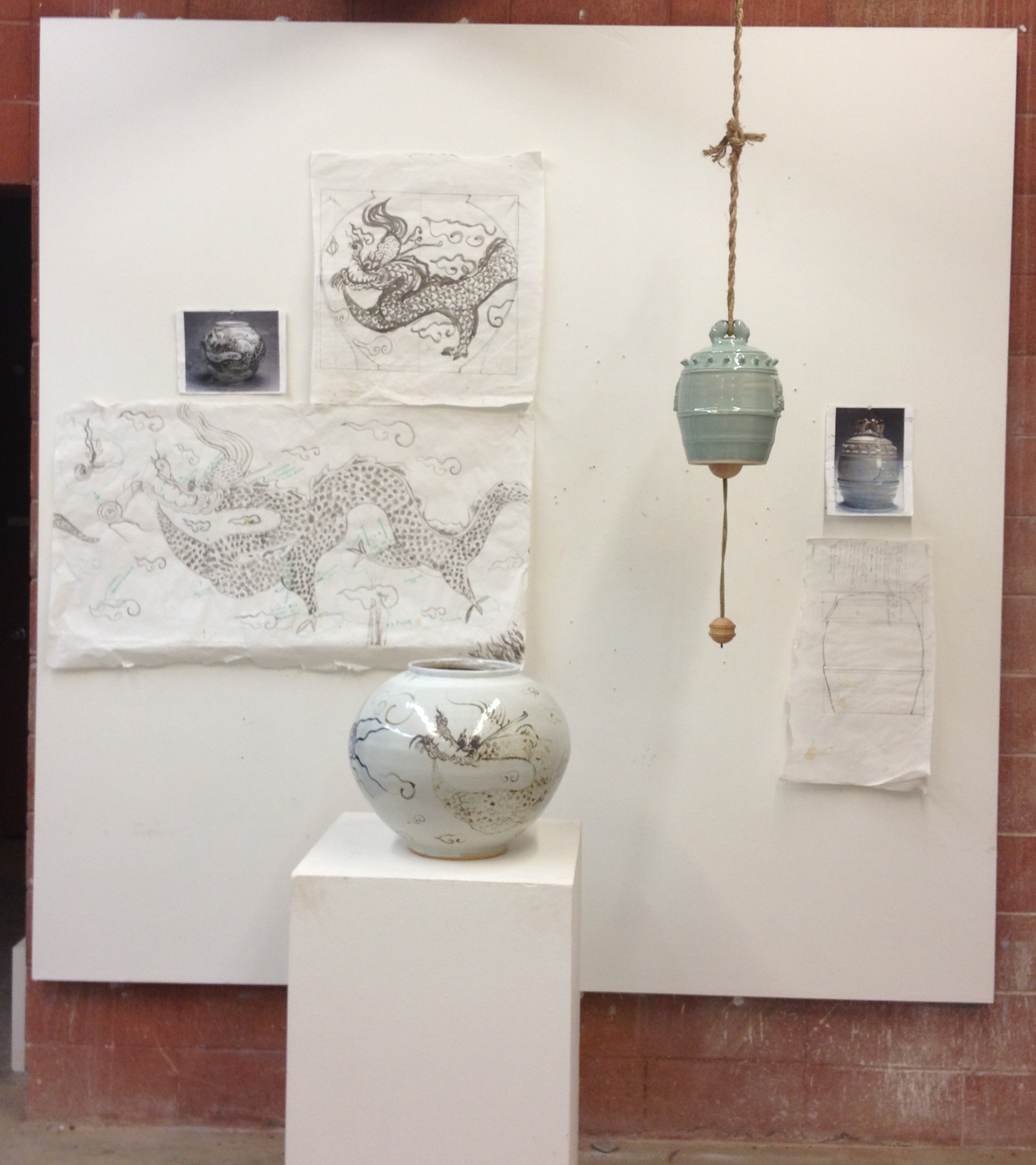 One student's work showing both his decorative brushwork pot, and carved celadon pot (actually a bell), both found in the Asian Art Museum in San Francisco. On the wall behind each piece are the preparatory sketches and diagrams he used to help create the pots.