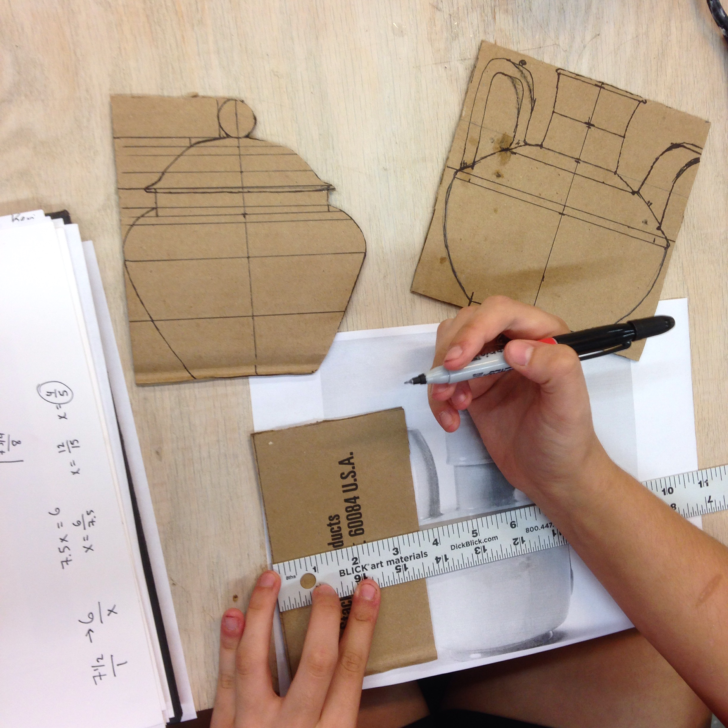 One student works out the proportions and scale of her chosen pot by measuring a print of the original pot and translating it onto a cardboard template.