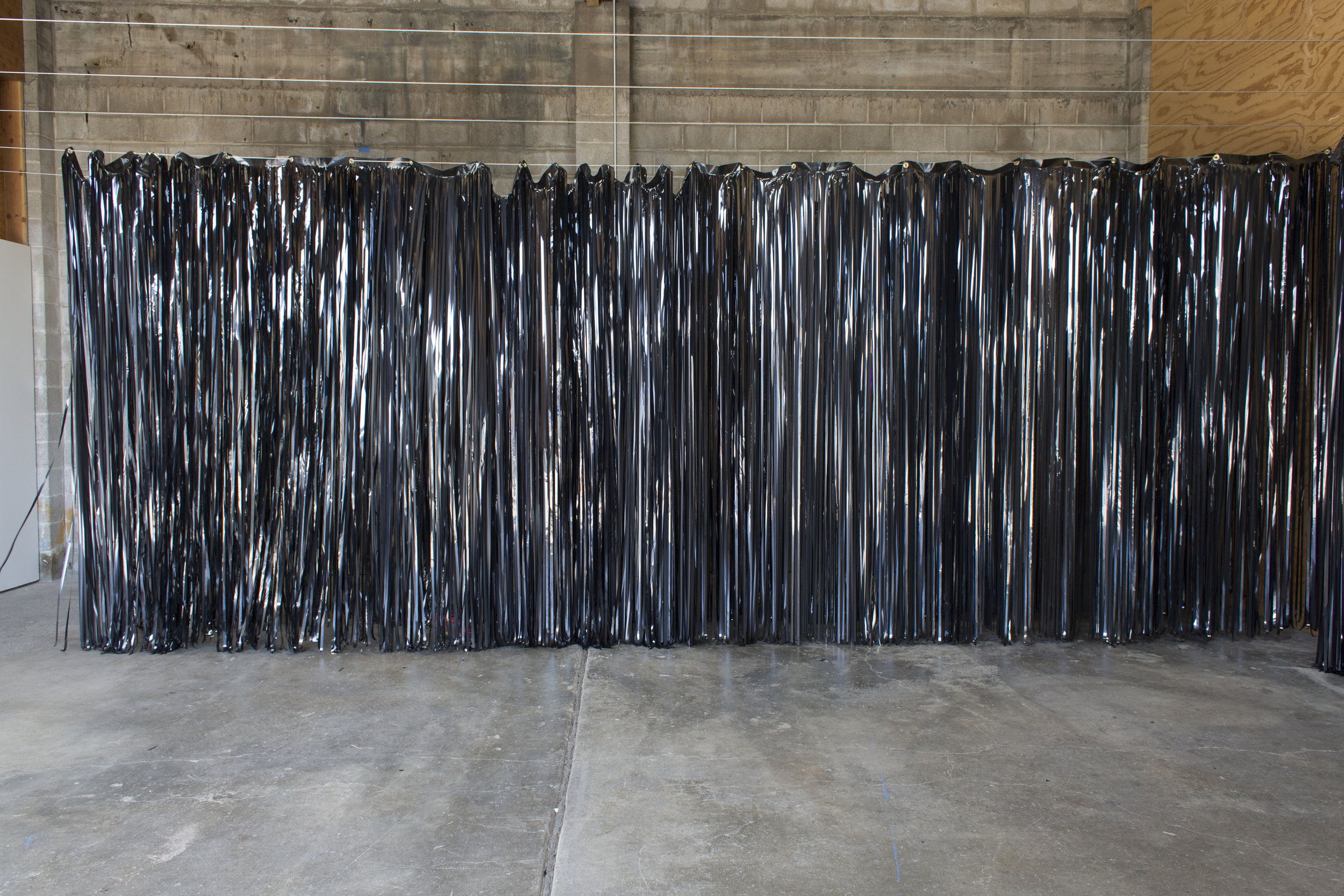 "To Look at an Object is to Plunge Oneself Into It  , 2017  VHS tape, wire, grommets  26.2 miles worth of VHS tape, strung out from 301 movies, fashioned into curtains.  For a full list of the movies, see the accompanying video ""Oblique and Autonomous."""