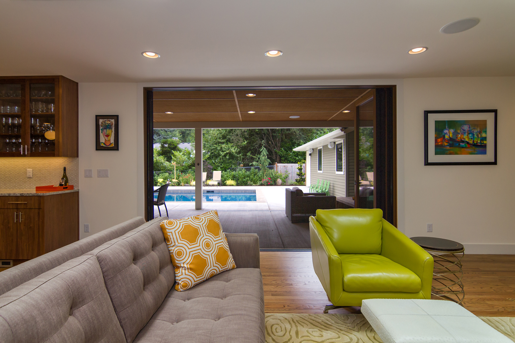 Through the La Cantina doors to exteriorliving space under covered veranda and pool. Lot was regraded for seamless transition inspired by universal design.