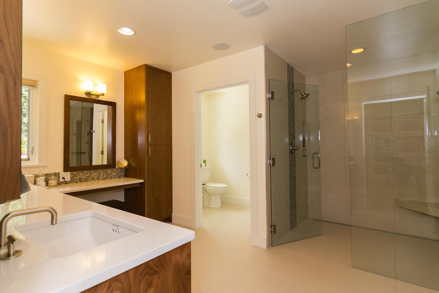 New master bathroom with no-thresholdglass shower enclosure, heated stone floors, vanity station, and custom walnut cabinets