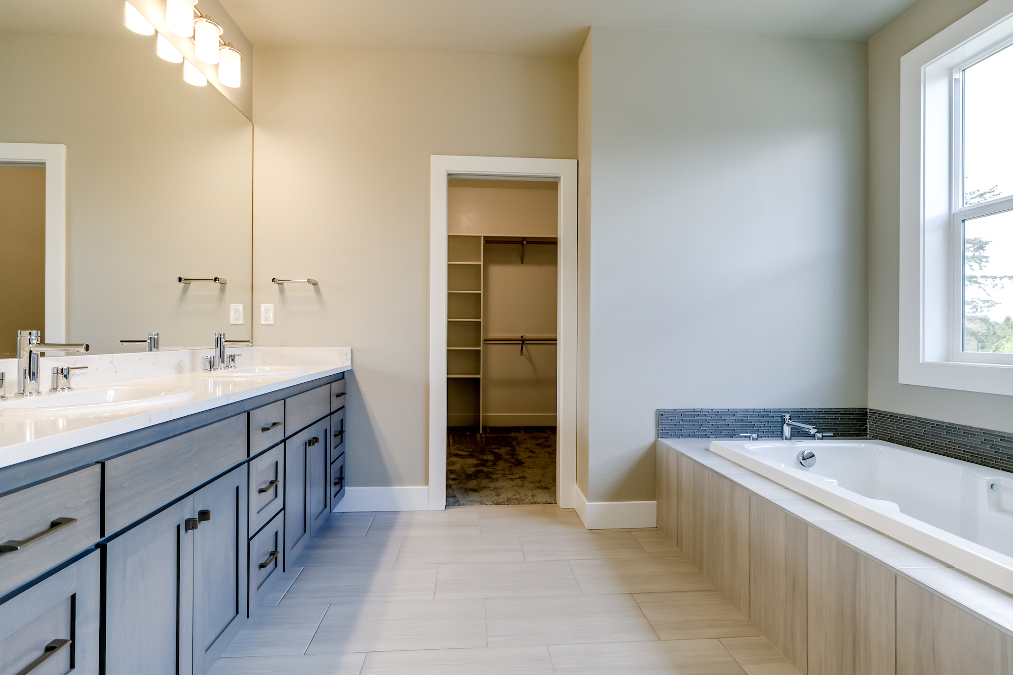 This master bathroom includes a soaker tub, 2 headed custom shower and walk in closet.