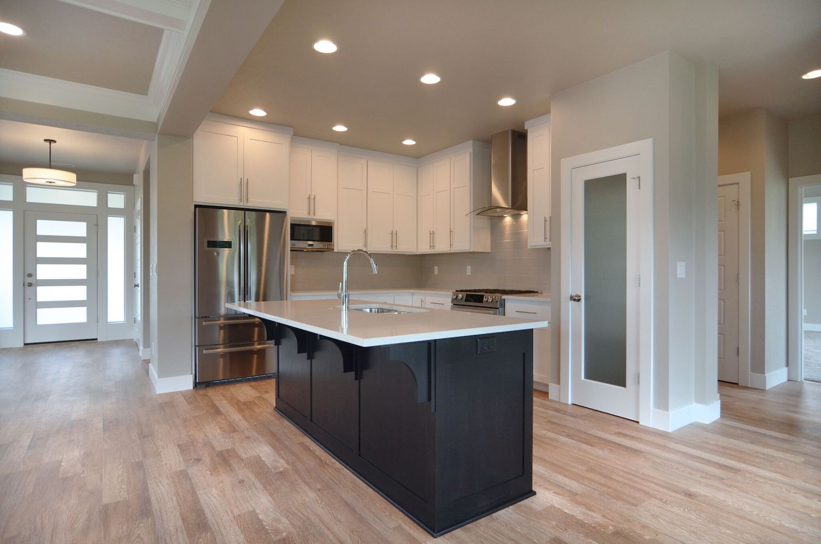 View of front entry, chef's kitchen and hallway to the master bedroom suite.