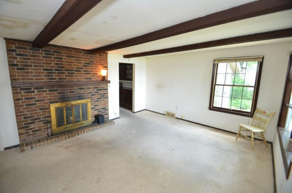 Family room off of kitchen with a non-functioning fireplace.