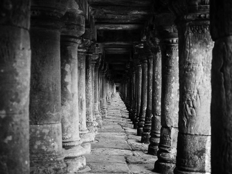 Underneath an elevated walkway leading to another temple