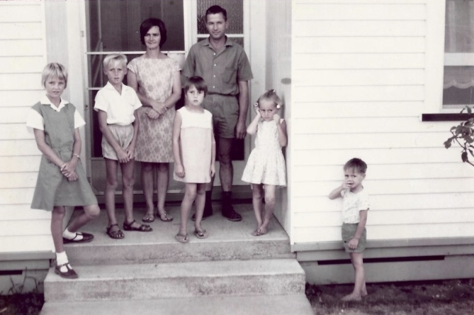 Cliff standing with his young family on the front steps of their home