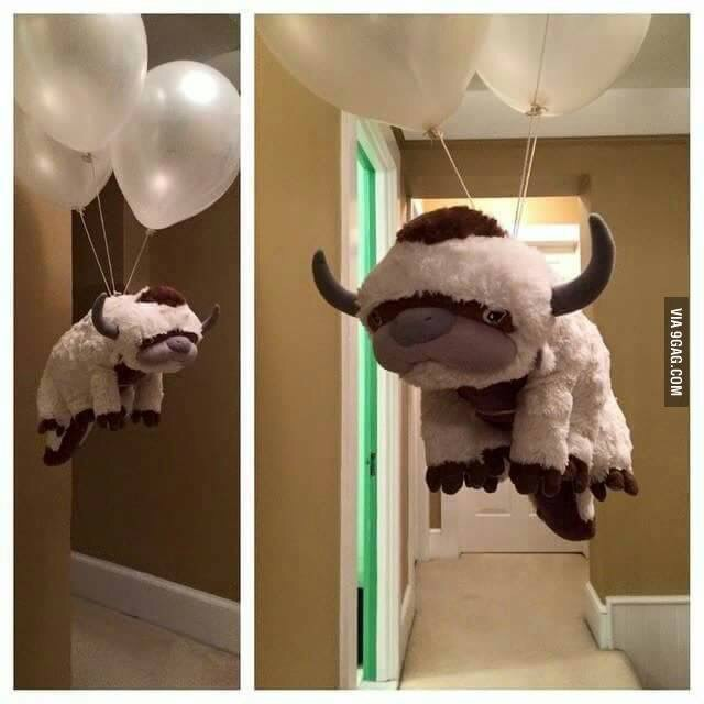 A plushie Appa is flying through a house, held aloft by a bunch of white, helium filled balloons.  This is an excellent idea.
