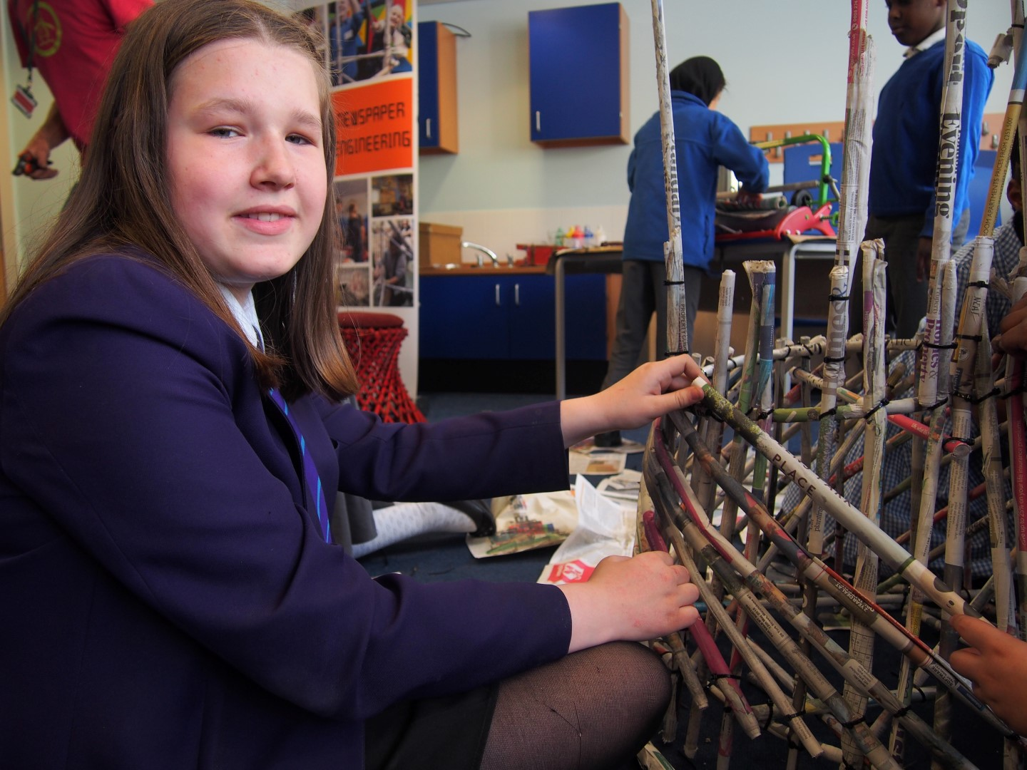 A pupil from a local secondary school helps out on the Newspaper Engineering activity at Willow Bank Primary Steam Co. Day