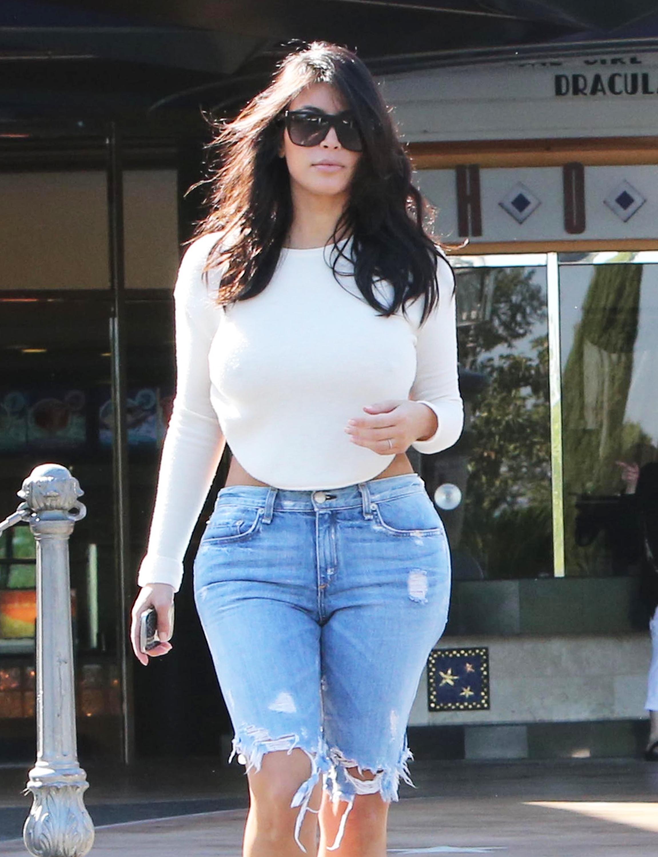 Kim Kardashian wearing a fitted distressed knee length shorts (photo credit: Huffington Post)