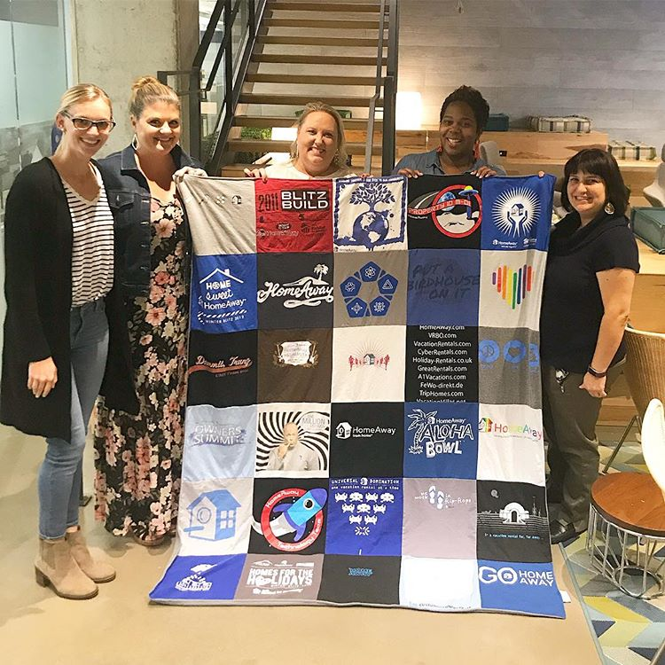 Tiffany (center) showing off her t-shirt quilt made from HomeAway shirts she's collected during her 11 years with the company.