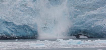 A part of a glacier falls into the ocean.