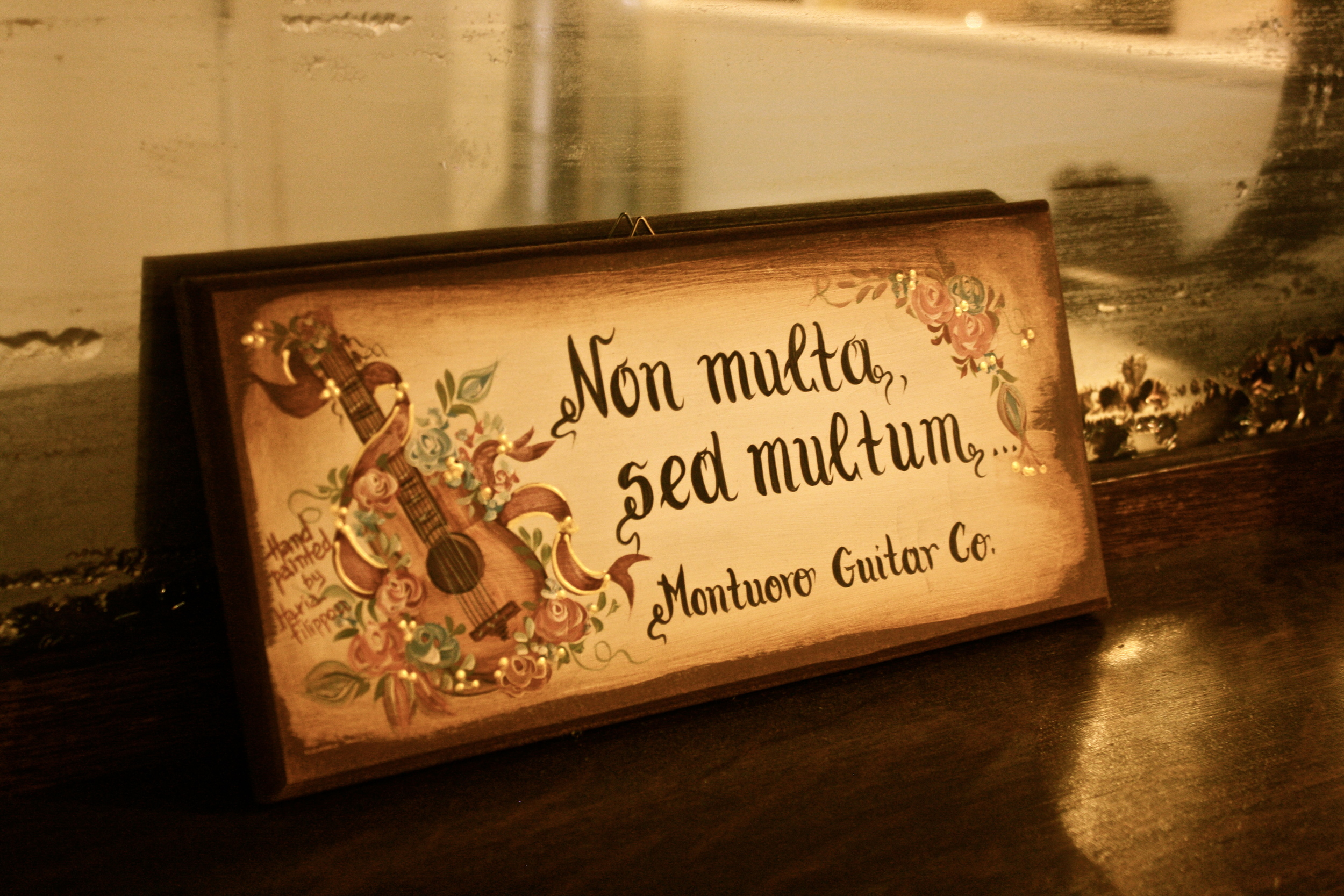 """The Latin translation is """"not many but much"""". The phrase popularized in the guitar world by the Frank Henry Martin carving at the Martin factory. This version a beautiful hand painted gift from a client."""