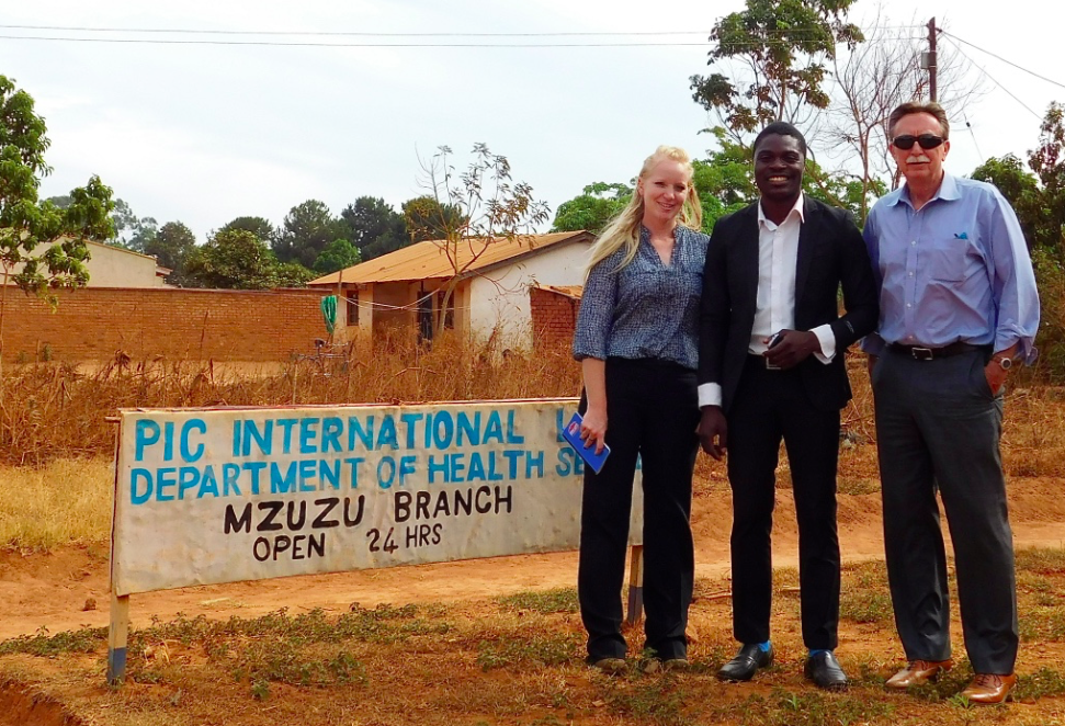 Kondwani Ngwira poses in front of the sign for his clinic, PIC International Health Center in Mzuzu with Wayne Decker and Angel Allen.
