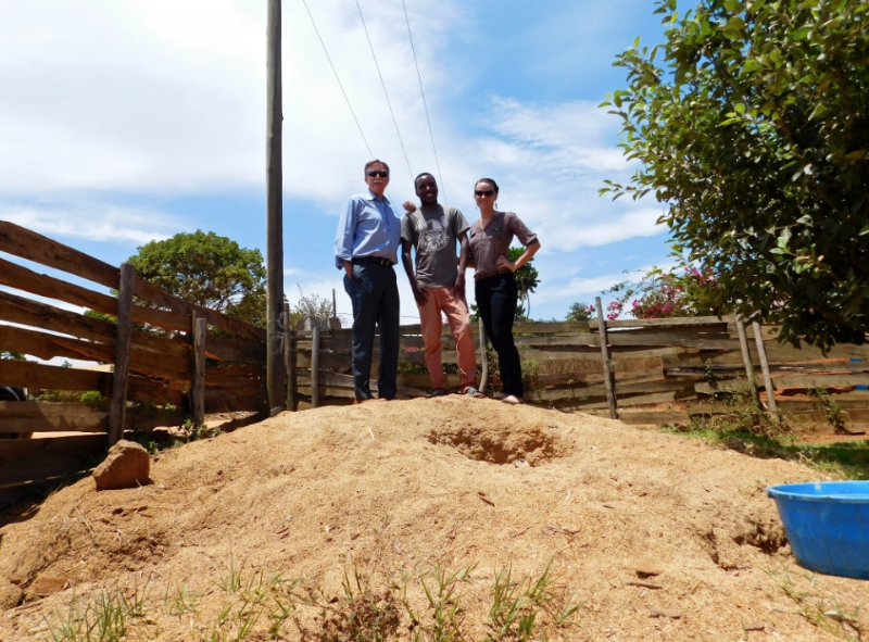 Wayne, Sungani, and Lauren stand atop the sawdust hill that feeds Green Heat Malawi's briquette production.