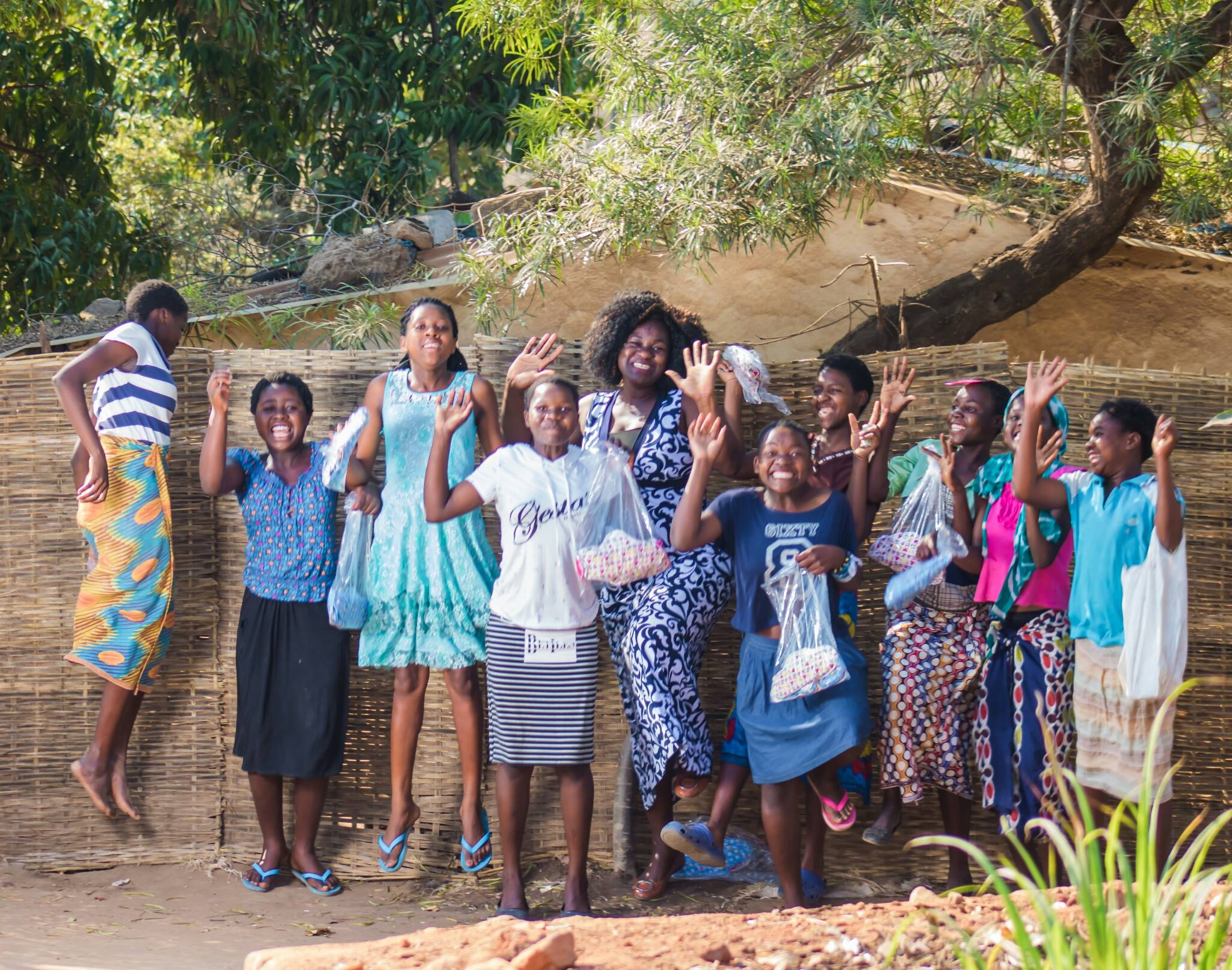 Trinitas Mhango participated in Flame Tree Initiative's Development Entrepreneurship Lab in 2016. Her social enterprise, Tina Pads, supports adolescent girls in Malawi to stay in school by delivering reproductive health education and reusable sanitary pads. Here, she is with young girls from Blantyre who were grateful and excited to receive pad packs from Tina Pads.