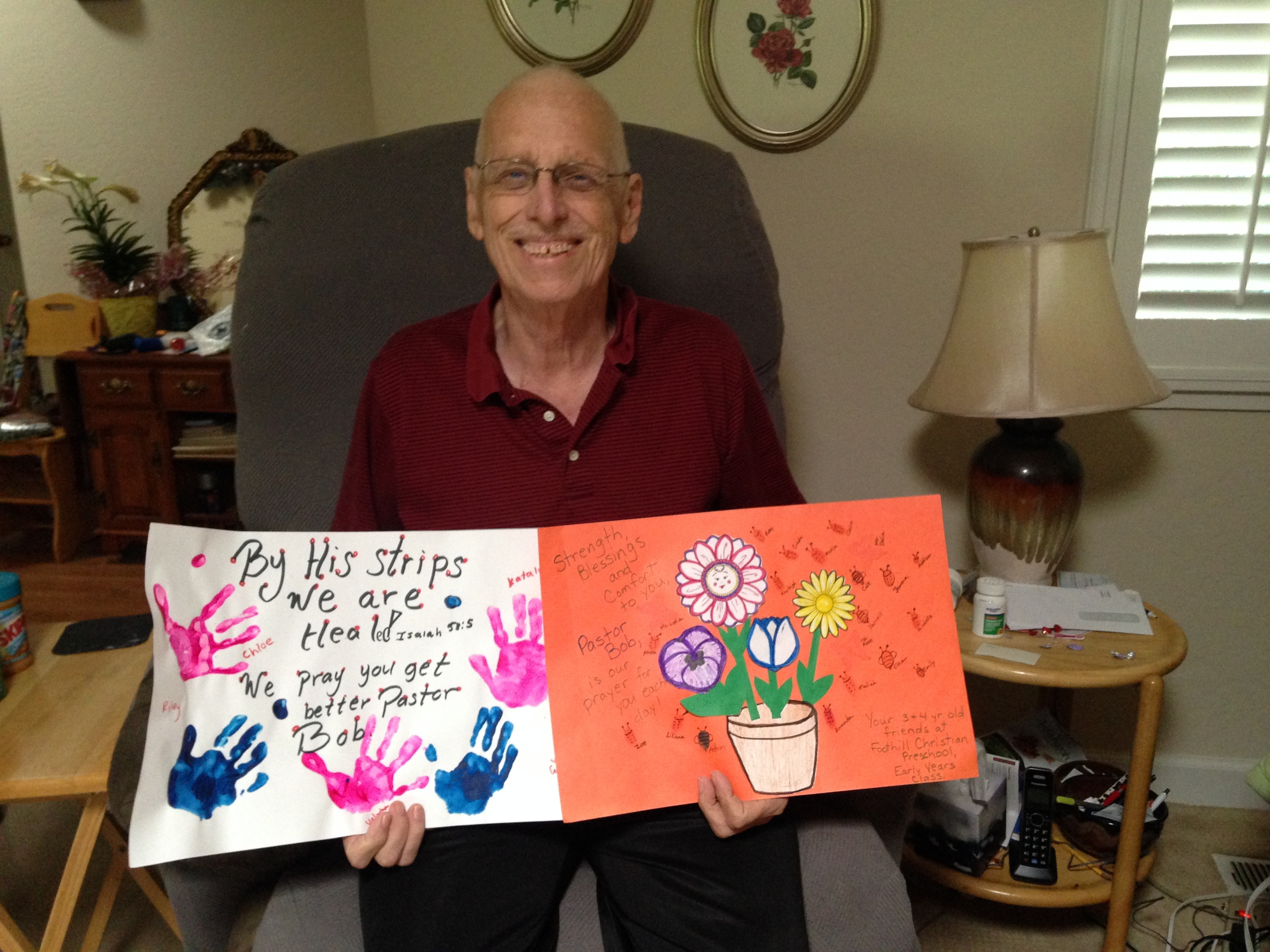 Pastor Bob, at home, holding cards that were made for him by the children of Foothill Christian Preschool