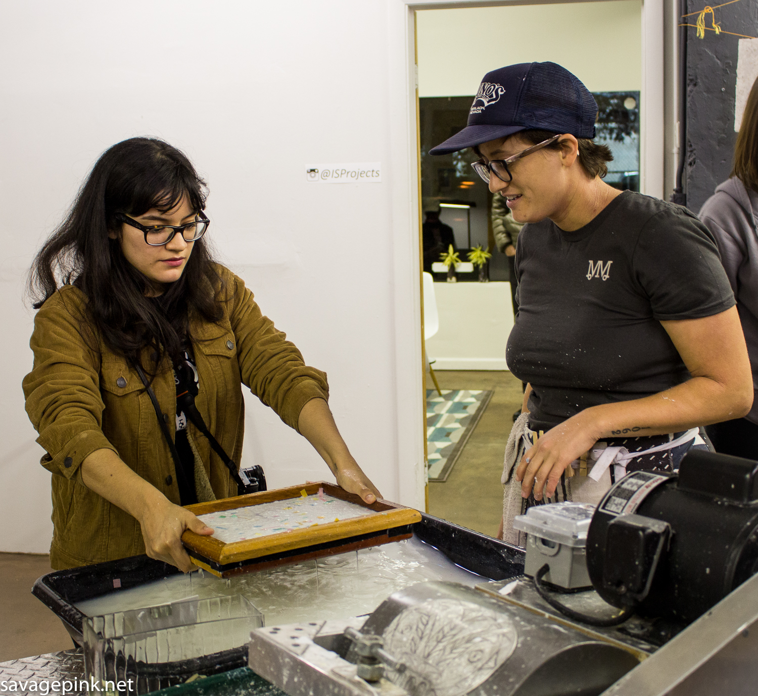 Jillian shows a visitor how to fill a frame with pulp to create a sheet of paper.