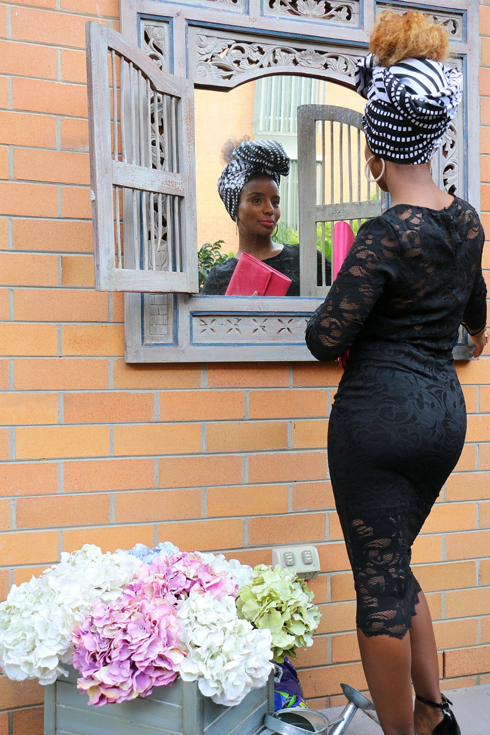 Brand ambassador YENI N wears  headwrap GUGU  teamed with a black lace outfit from popular fashion retailer  H&M .
