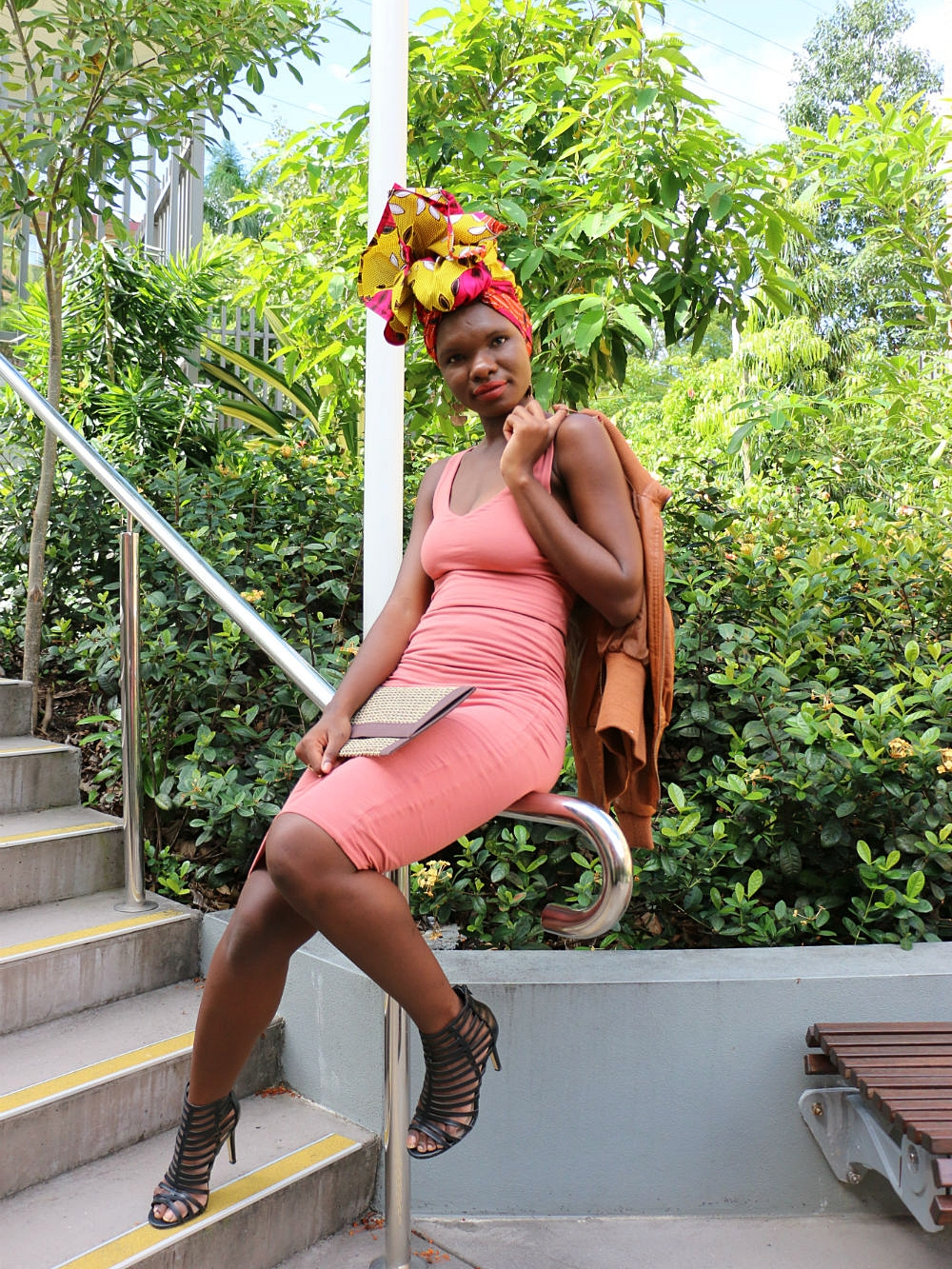 Guided by our mood board, brand ambassador ISATA T found this lovely salmon coloured body-con top and matching skirt in her wardrobe. Black heels, a tan bomber jacket and clutch complete this chic look and totally makes the colours pop on  headwrap TAMARA.