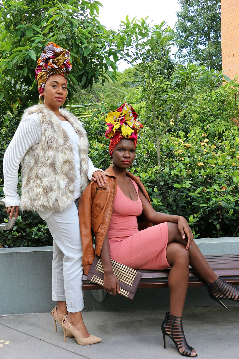 Brand ambassador GRACEY B (standing) teamed her cream cargo pants with a faux fur nude sleeveless jacket, cream loose-fitting jumper and nude heels to highlight the colour palette in headwrap SHERRI. ISATA T is seated beside GRACEY B wearing headwrap TAMARA.