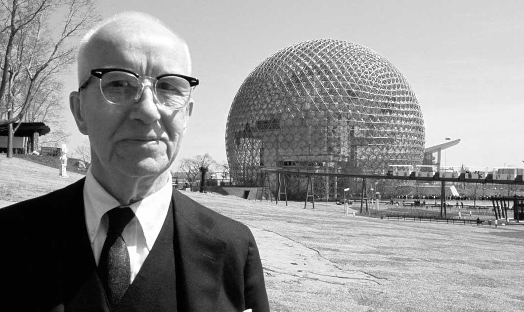 Buckminster Fuller en un tres piezas. Al fondo su cúpula geodésica.