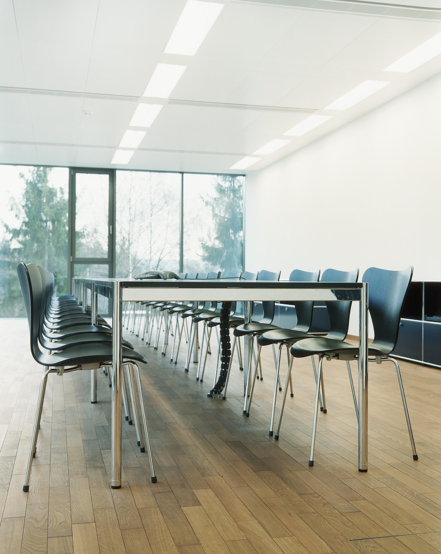 Puristischer Konferenzraum mit Blick ins Grüne.